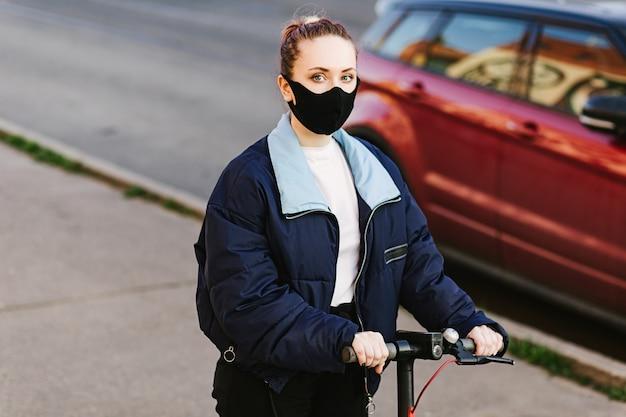 Mulher com uma máscara protetora com patinete elétrico tecnológico