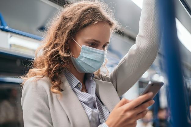 Mulher com uma máscara protetora de pé em um trem do metrô.