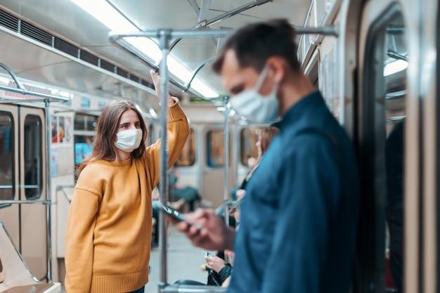 Mulher com uma máscara protetora em um vagão do metrô