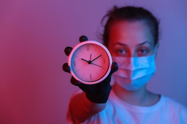 Mulher com uma máscara protetora, luvas detém relógio. luz de néon gradiente vermelho azul