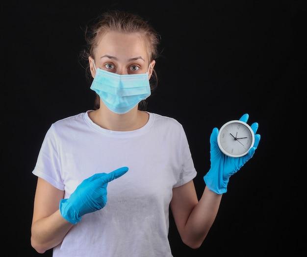 Mulher com uma máscara protetora médica, luvas segurar um relógio branco em uma parede preta.