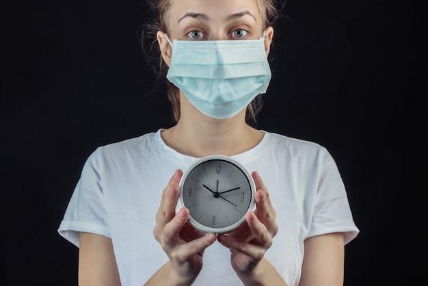 Mulher com uma máscara protetora médica segurando um relógio branco em uma parede preta.