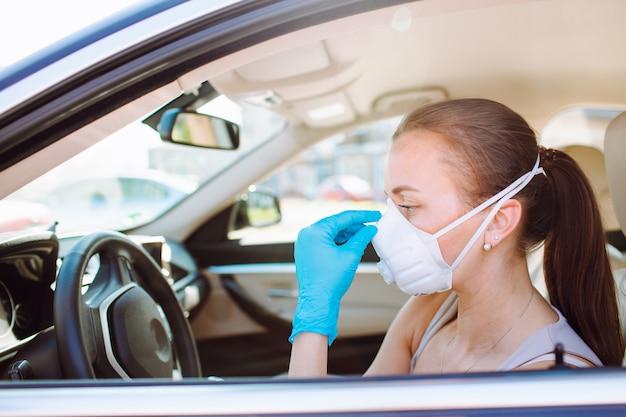 Mulher com uma máscara protetora no rosto no carro