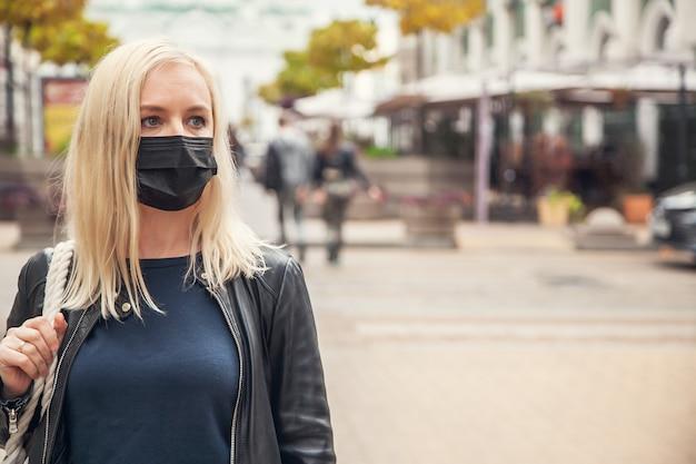 Mulher com uma máscara protetora preta contra o pano de fundo da cidade.