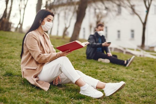 Mulher com uma máscara, sentado em uma grama