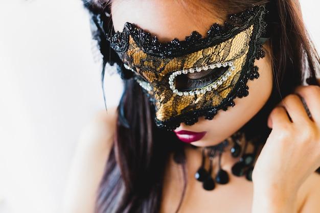 Mulher com uma máscara veneziana de ouro e um chapéu preto em um fundo branco