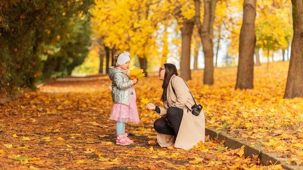 Mulher com uma menina caminha no parque de outono e tira fotos contra o fundo de uma folhagem de outono amarela brilhante