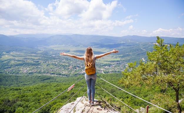 Mulher com uma mochila amarela olhando uma bela vista da montanha