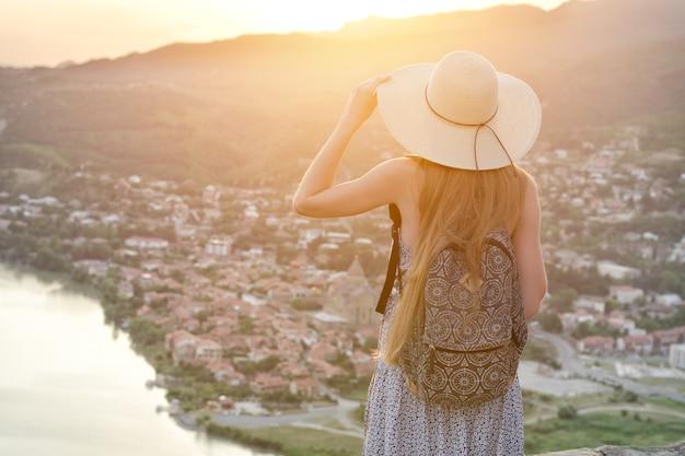Mulher com uma mochila e um chapéu olha para a cidade e o rio abaixo.