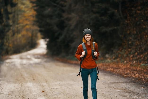 Mulher com uma mochila em pleno crescimento caminha ao longo da estrada na floresta no outono