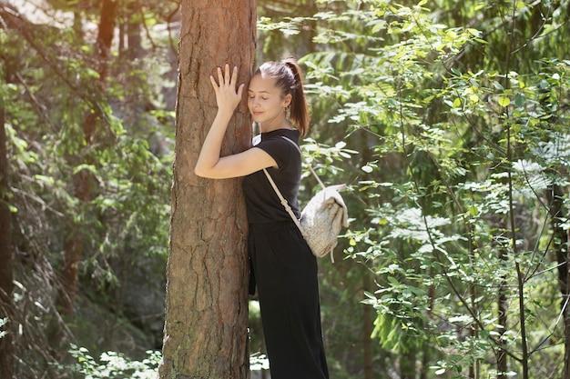 Mulher com uma mochila está abraçando uma árvore com os olhos fechados na floresta. dia de sol de verão.