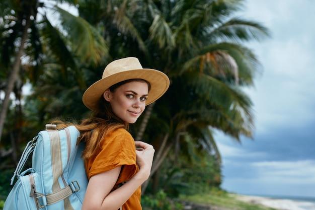 Mulher com uma mochila perto das árvores sobre a natureza de uma ilha