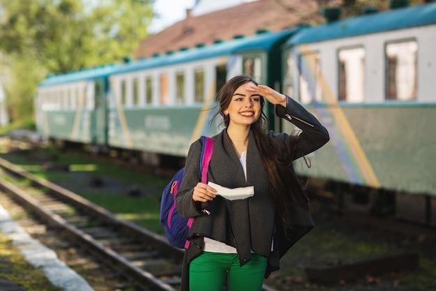 Mulher com uma mochila, perto do trem verifica seu bilhete para a plataforma da estação