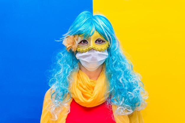 Mulher com uma peruca azul e máscara de carnaval amarelo, vestindo uma máscara de saúde médica da coroa do vírus