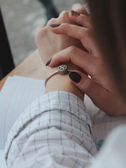 Mulher com uma pulseira de prata da moda com um pingente