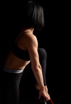 Mulher com uma roupa de esportes fazendo exercícios
