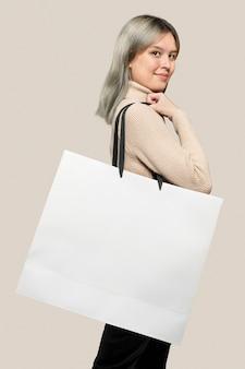 Mulher com uma sacola de compras branca com espaço de design