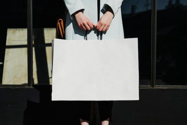 Mulher com uma sacola de compras depois de uma farra de gastos