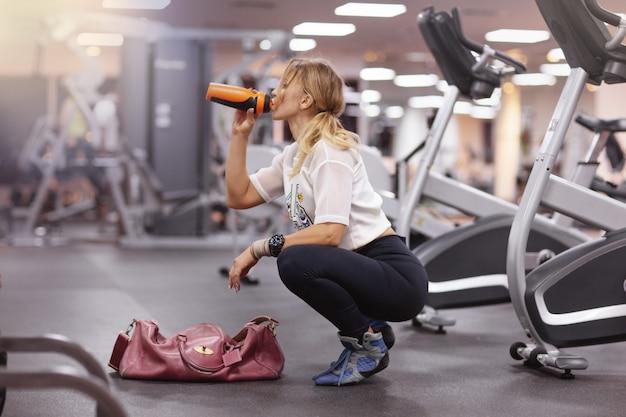 Mulher com uma sacola vermelha bebe água de uma coqueteleira na academia