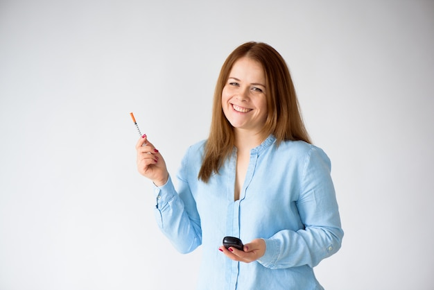 Mulher com uma seringa da insulina isolada no conceito branco do fundo do diabetes.