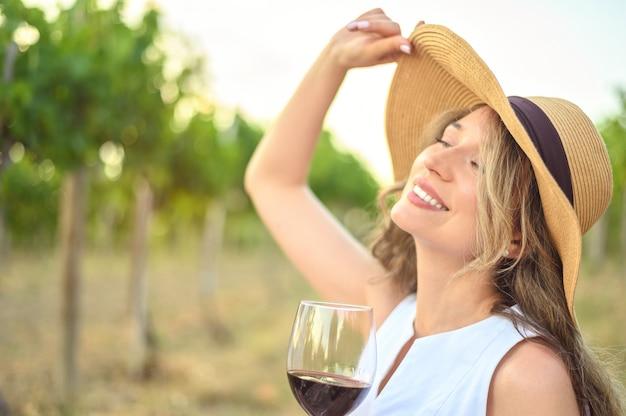 Mulher com uma taça de vinho sonhadora parece garota feliz bebendo vinho.