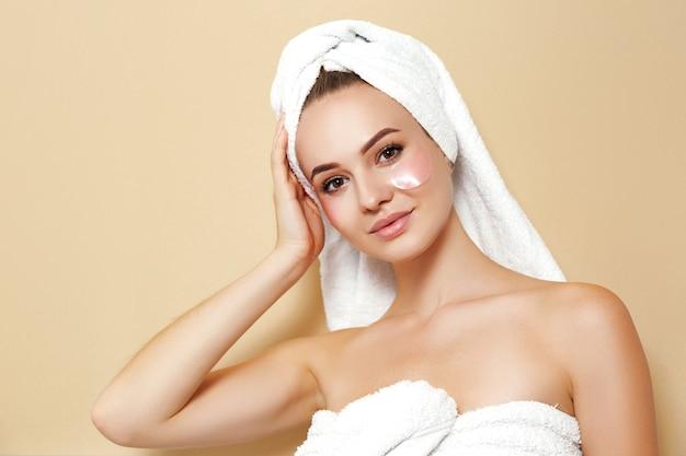 Mulher com uma toalha branca com manchas no rosto posando