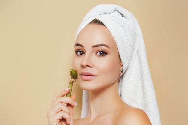 Mulher com uma toalha branca na cabeça e um massageador facial de jade nas mãos
