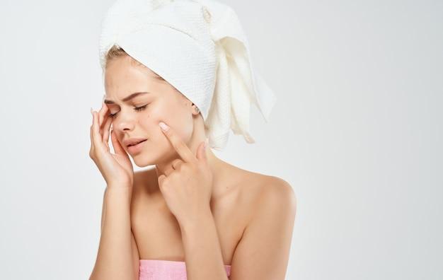 Mulher com uma toalha branca na cabeça tocando seu rosto com as mãos em uma luz