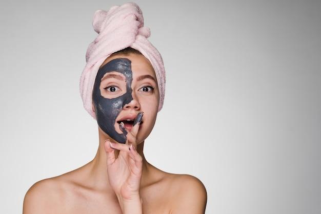 Mulher com uma toalha na cabeça colocou uma máscara no rosto