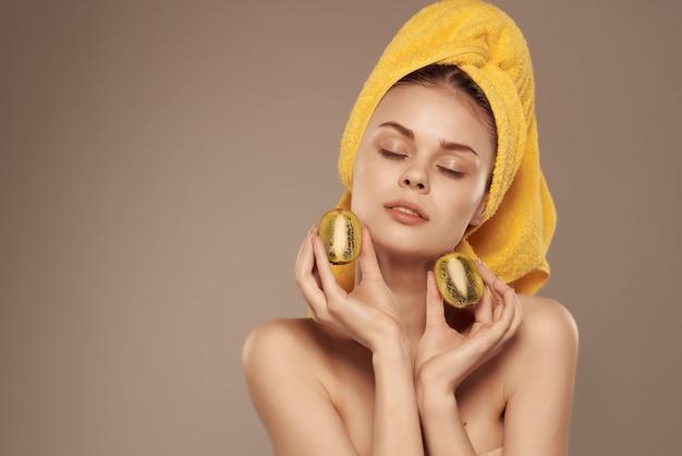 Mulher com uma toalha na cabeça, cuidados com a pele, kiwi, vista recortada