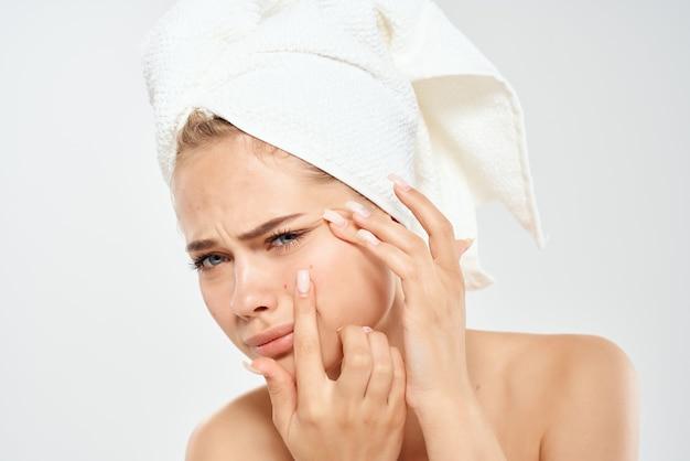 Mulher com uma toalha na cabeça descontente problemas de pele luz de fundo