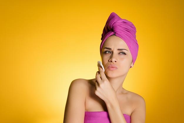 Mulher com uma toalha na cabeça remove a maquiagem com um disco de algodão
