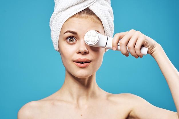 Mulher com uma toalha na cabeça segura massageadores nas mãos perto do relaxamento de cosmetologia facial.
