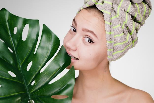 Mulher com uma toalha na cabeça segurando uma grande folha verde