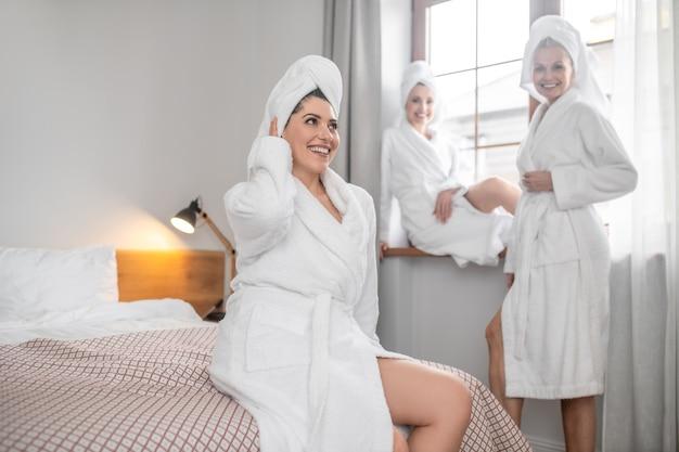 Mulher com uma toalha na cabeça tocando com a mão