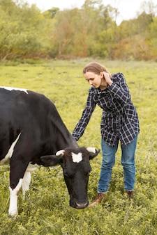 Mulher com uma vaca na fazenda