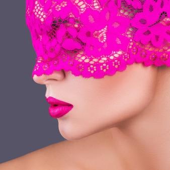Mulher com uma venda rosa no rosto