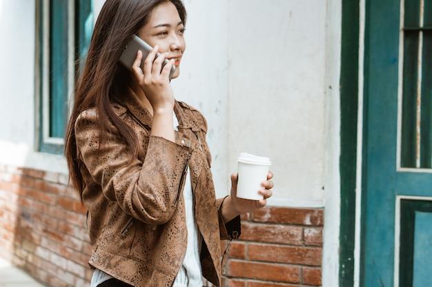 Mulher com uma xícara de café andando e chamando