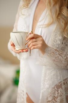 Mulher com uma xícara de café, modelo de boudoir, manhã de casamento da noiva linda
