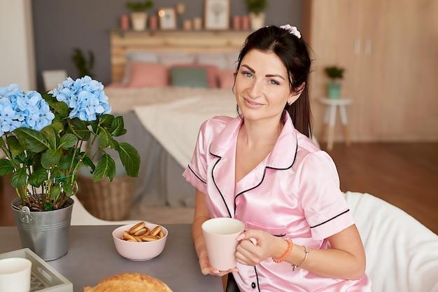 Mulher com uma xícara de café na manhã em casa.