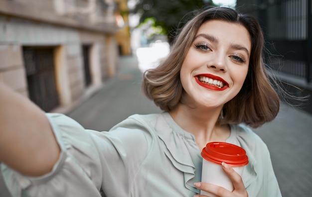 Mulher com uma xícara de café na mão perto de um prédio de tijolos e maquiagem de verão em saia vermelha