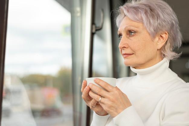Mulher com uma xícara de café, olhando pela janela