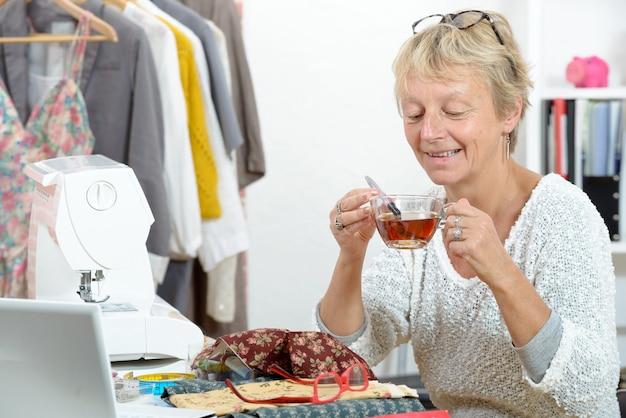 Mulher com uma xícara de chá em sua oficina de costura