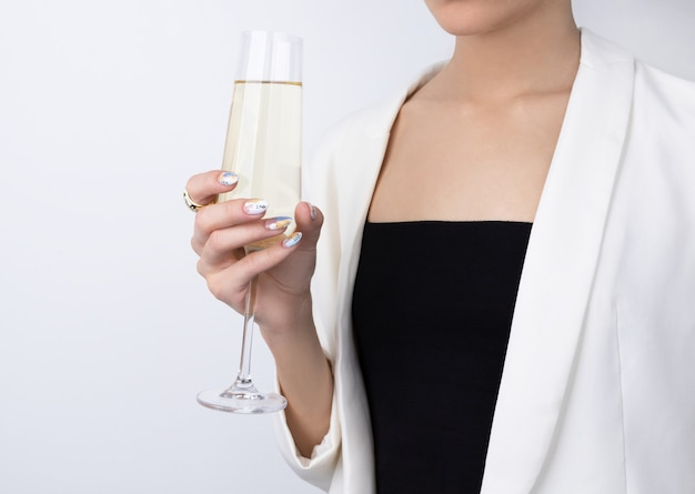 Mulher com unhas na moda cor pastel, segurando a taça de champanhe
