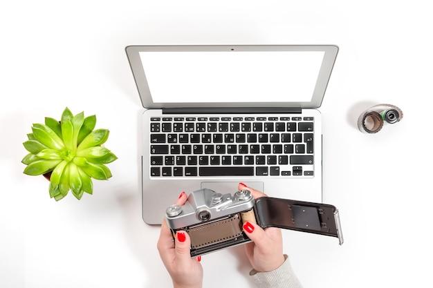 Mulher com unhas vermelhas segurando e abrindo a câmera de filme vintage e trabalhando no laptop moderno perto do vaso e branco.