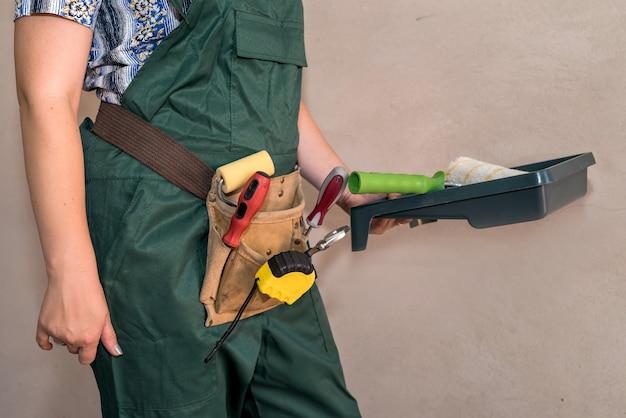Mulher com uniforme de proteção mostrando ferramentas de pintura