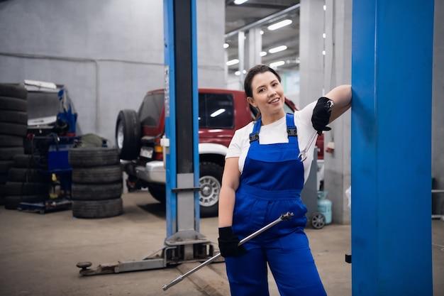 Mulher com uniforme de trabalho segurando uma chave inglesa e sorrindo