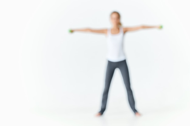 Mulher com uniforme esportivo com halteres nas mãos, treino de motivação corpo esguio