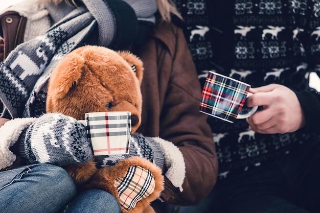 Mulher com ursinho de pelúcia e homem estão sentados com copos de bebidas quentes em roupas quentes no inverno