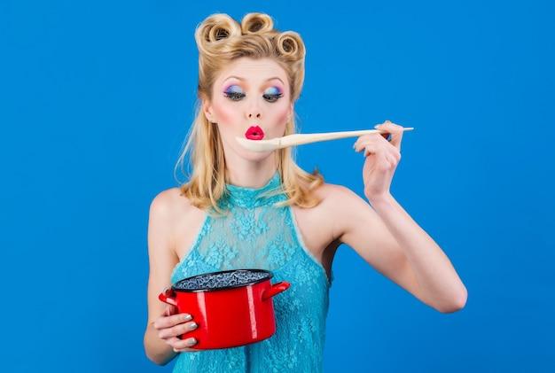 Mulher com utensílios de cozinha na cozinha. dona de casa de estilo retro com panela e colher. cozinha, culinária, conceito doméstico.